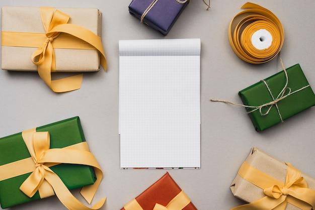 Flache lage des notizbuchmodells mit weihnachtsgeschenken