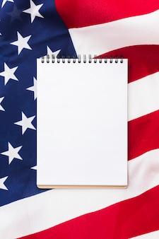 Flache lage des notizbuchs oben auf amerikanischer flagge