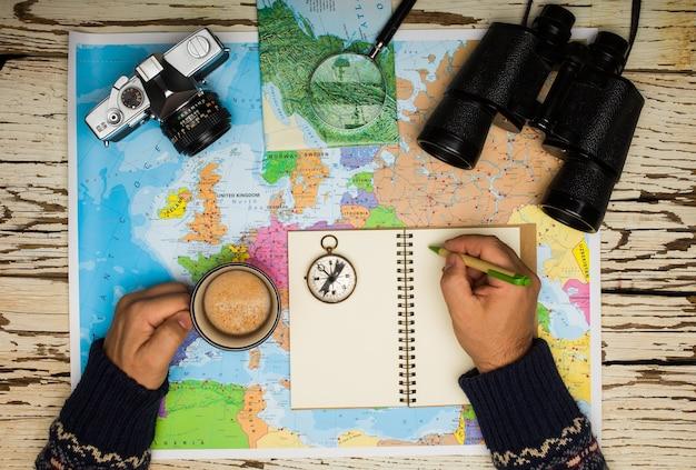 Flache lage des reiseplanungskonzepts. draufsicht der mannhände, die auf einem tagebuch, auf dem tischfernglas, kompass, retro-fotokamera, kaffee und europakarte auf einem weißen holztisch schreiben