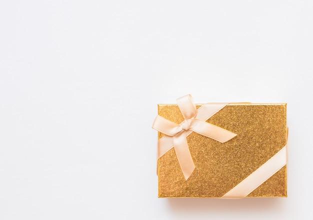 Flache lage des romantischen geschenks verziert mit band auf gelbem hintergrund