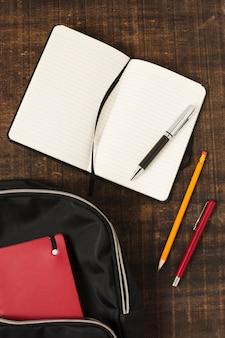Flache lage des rucksacks mit briefpapierzubehör