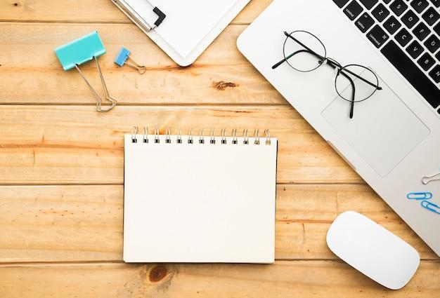 Flache lage des schreibtischdesigns mit notizbuch