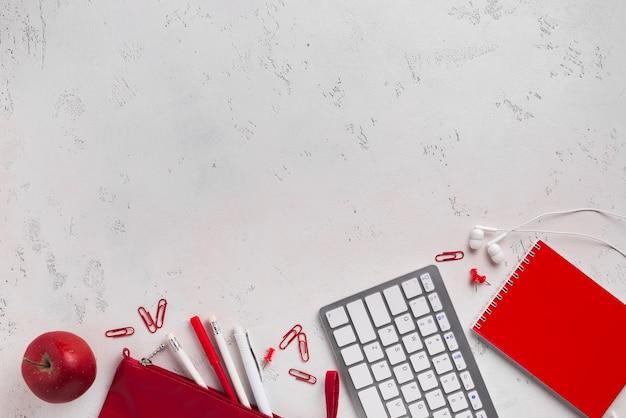 Flache lage des schreibtisches mit apfel und tastatur