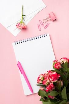 Flache lage des schreibtisches mit notizbuch und rosenstrauß