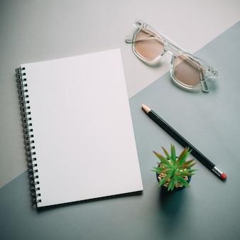 Flache lage des schreibtischs des minimalen arbeitsplatzes mit notizbuch, brillen und grünpflanze