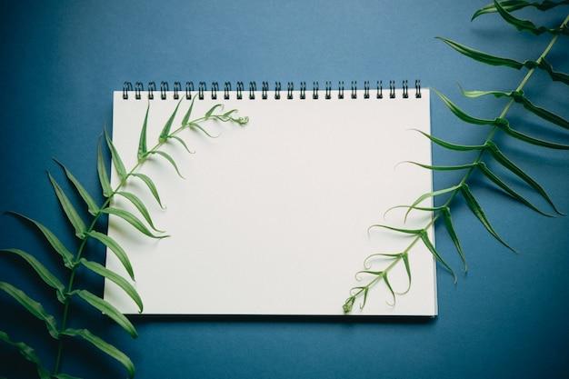 Flache lage des schreibtischs des minimalen arbeitsplatzes mit notizbuch und grünpflanze, auf tiefem blauem ton