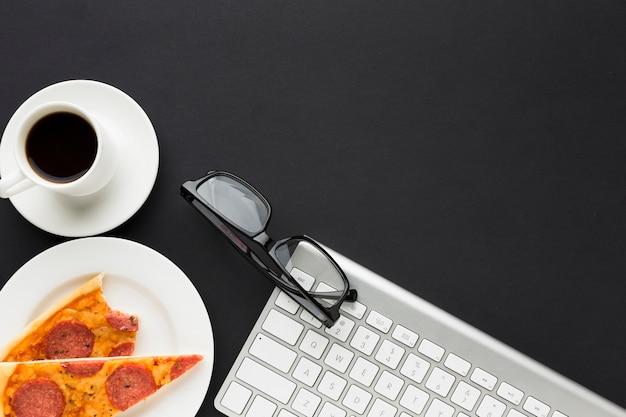 Flache lage des schreibtischs mit pizza und tastatur
