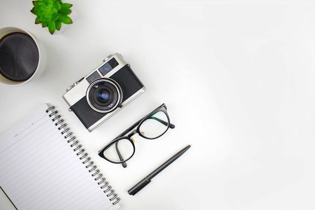 Flache lage des schreibtischs mit reisezubehör, filmkameras, gläsern, notizbüchern und kaffee. mit textfreiraum.