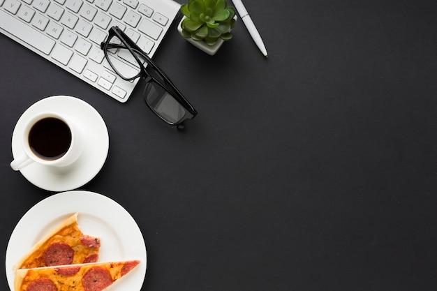 Flache lage des schreibtischs mit tastatur und pizza