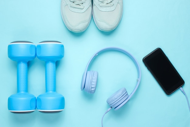 Flache lage des smartphones mit kopfhörern, plastikhanteln, sportschuhen