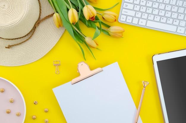 Flache lage des sommerhintergrundes von gelben tulpen mit tablettentastatur und -klemmbrett