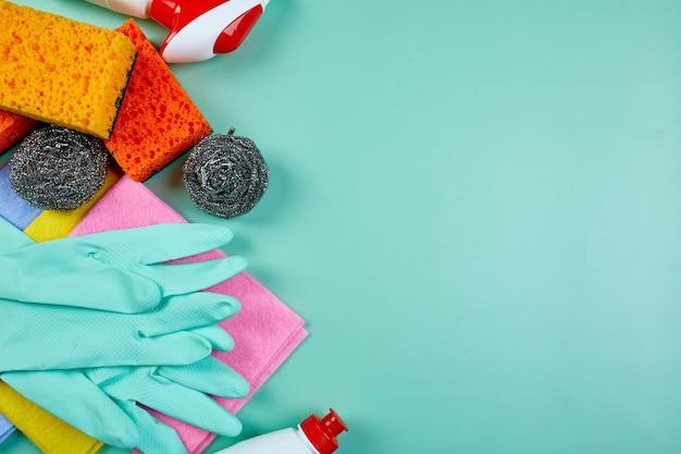 Flache lage des sortenhausreinigungsprodukts auf blauem tisch mit kopierraum, reinigungsset für verschiedene oberflächen, reinigungsmittel-servicekonzept, draufsicht.