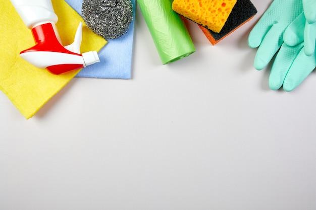 Flache lage des sortenhausreinigungsprodukts auf grauem tisch mit kopierraum, reinigungsset für verschiedene oberflächen, reinigungsmittel-servicekonzept, draufsicht.