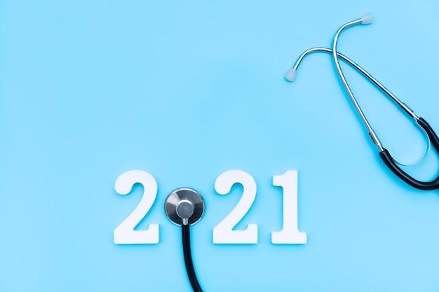 Flache lage des stethoskops und der zahl auf medizinischem konzept des blauen hintergrundgesundheitskopierraums draufsicht