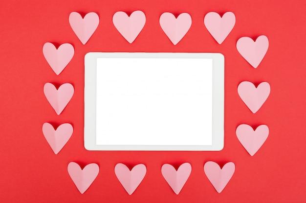 Flache lage des tablet-computers mit leerem bildschirm auf rotem hintergrund mit papierherzen