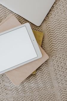 Flache lage des tablet-pads auf einer decke mit notizbüchern. bildschirmanzeige für leere kopienraumvorlagen