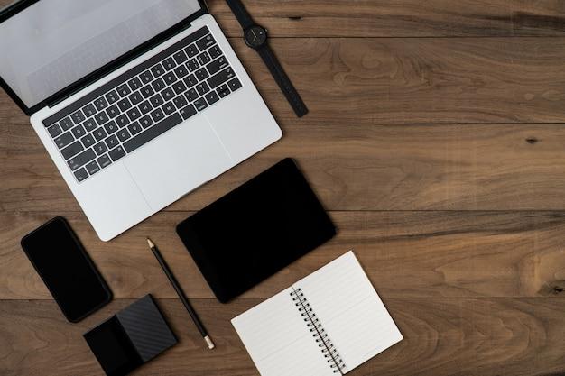 Flache lage des technologiegegenstandes auf tabelle mit laptop-computer-notizbuch smartphone-festplattenlaufwerkssicherung und -bleistift.