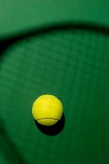 Flache lage des tennisballs mit schlägerschatten