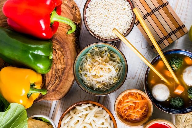 Flache lage des thailändischen köstlichen lebensmittels mit buntem grünem pfeffer auf baumstumpf