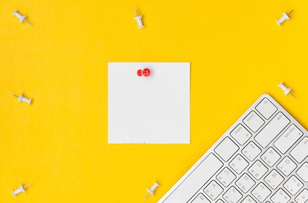 Flache lage des tischplattenarbeitsplatzes mit dem roten druckbolzen, der auf dem weißbuch der leerstelle notiert wurde und der tastatur auf gelbem hintergrund klebrig ist