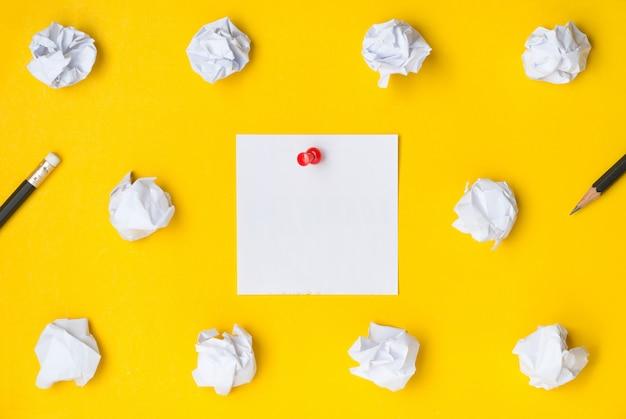 Flache lage des tischplattenarbeitsplatzes mit dem roten druckbolzen, der auf dem weißbuch klebrig ist, merkte auf gelbem hintergrund
