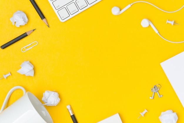 Flache lage des tischplattenarbeitsplatzes mit leerstellepapierblatt auf gelbem hintergrund