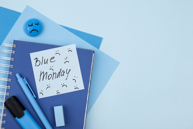 Flache lage des traurigen gesichts des blauen montags mit notizbuch und marker