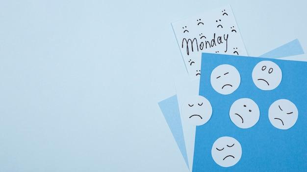 Flache lage des traurigen gesichts für blauen montag mit haftnotiz