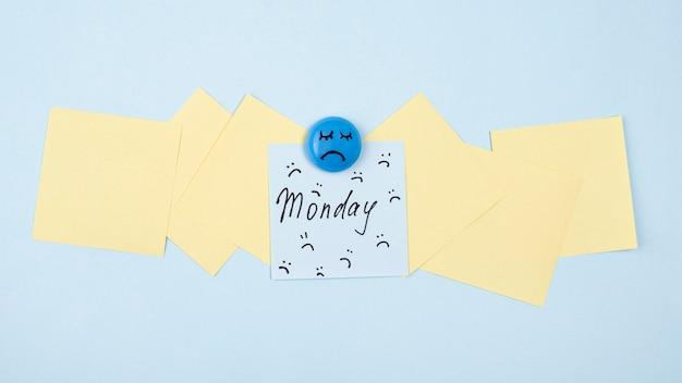 Flache lage des traurigen gesichts mit haftnotiz für blauen montag