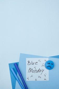 Flache lage des traurigen gesichts mit stiften für blauen montag