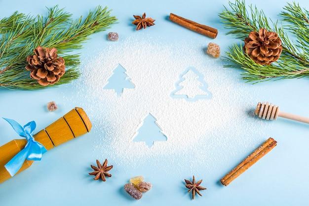 Flache lage des weihnachtsbackens. küchenutensilien für hausgemachtes kochen und christbaumzweig mit zapfen