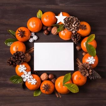Flache lage des weihnachtskranzes machen von mandarinen und tannenzapfen mit leerem papier