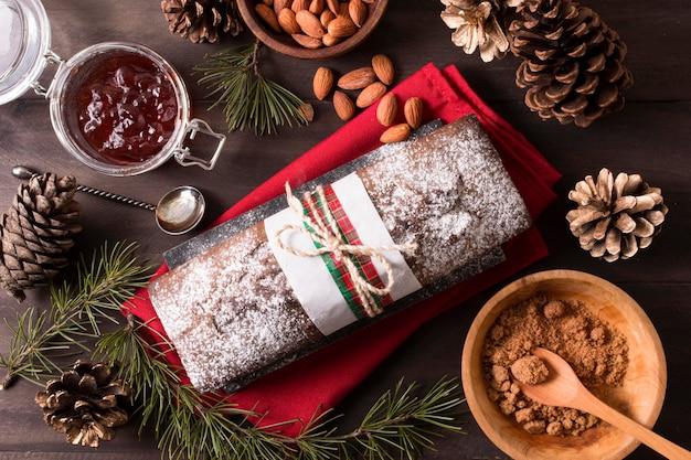 Flache lage des weihnachtskuchens mit mandeln und tannenzapfen