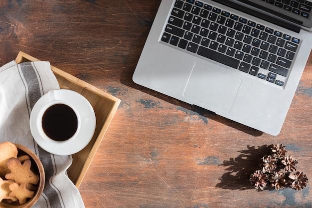 Flache lage des weihnachtstannenbaumasts, des lebkuchenmannes, der kaffeetasse und der computer- oder laptoptastatur auf hölzernem.