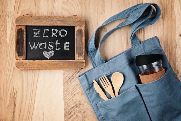 Flache lage des zero waste kits. set umweltfreundliches bambusbesteck, baumwolltasche. nachhaltiger, ethischer, plastikfreier lebensstil. draufsicht