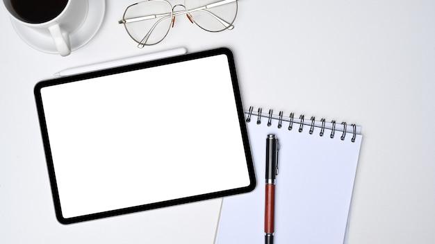 Flache lage, digitale tablette mit leerem bildschirm und notizbuch auf weißem schreibtisch.