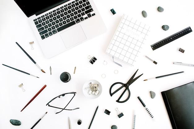 Flache lage, draufsicht bürotisch schreibtisch. arbeitsbereich mit notizbuch, laptop, schere, brille, stift auf weißem hintergrund.
