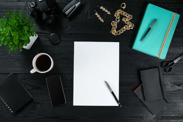 Flache lage, draufsicht bürotisch schreibtischrahmen. arbeitsbereich mit sauberem blatt papier, münztagebuch und mobilem gerät auf dunklem hintergrund.