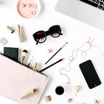 Flache lage, draufsicht bürotisch schreibtischrahmen. weiblicher schreibtischarbeitsplatz mit laptop, kupplung, kosmetik, telefon, sonnenbrille, lippenstift-rosenknospen auf weißem hintergrund.