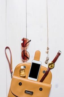 Flache lage, draufsicht, damenaccessoires fielen aus der beigen handtasche auf weißem hintergrund. telefon, uhren, sonnenbrillen, parfums