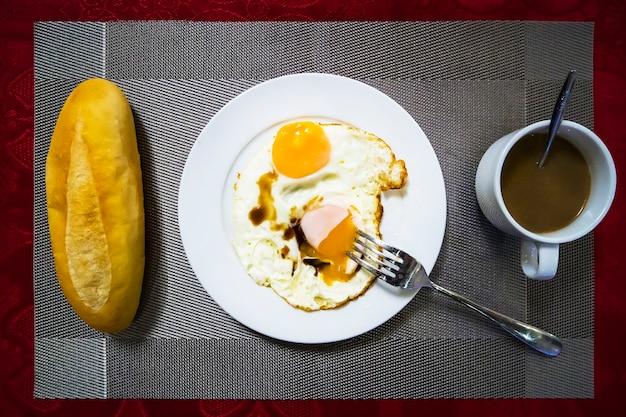 Flache lage, draufsicht frisches brot mit weizen, müsli und ei, milch, kaffee. französisches frühstück.