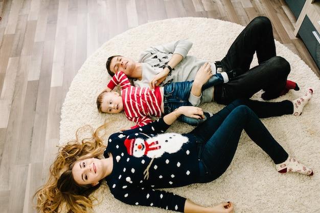 Flache lage, draufsicht. glückliche familie: mama, papa und kleiner sohn in santa claus-pullovern, auf dem boden liegend. liebe umarmungen genießen, urlaub menschen. zusammengehörigkeitskonzept. frohe weihnachten und ein glückliches neues jahr.