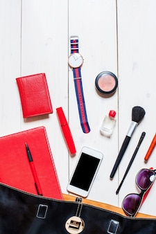 Flache lage, draufsicht, mock-up-kosmetik und damenaccessoires fielen aus der schwarzen handtasche auf weißem hintergrund. telefon, brille, uhr, notizbuch, stift