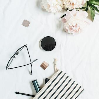Flache lage, draufsicht modeoberfläche mit pfingstrosenblumen, gläsern, kosmetika