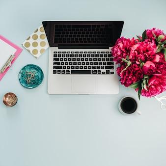 Flache lage, draufsicht weiblicher home-office-schreibtischarbeitsplatz mit blumenstrauß auf blauem hintergrund