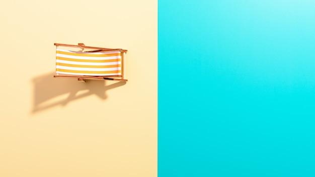 Flache lage einer komponierten miniatur des strandloungebereichs mit liegestuhl auf der farbenfrohen oberfläche