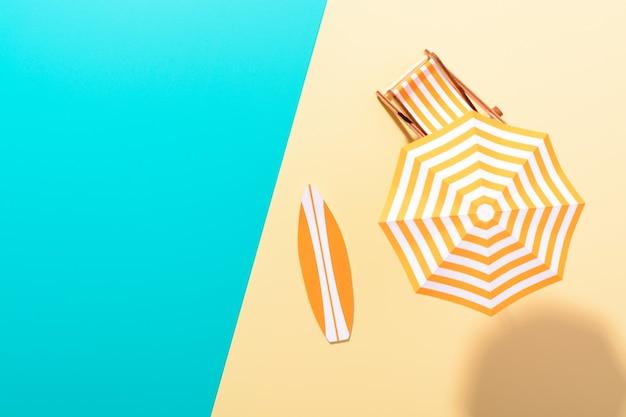 Flache lage einer komponierten miniatur des strandloungebereichs mit sonnenschirm und liegestuhl auf der farbenfrohen oberfläche