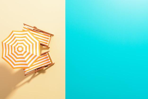 Flache lage einer komponierten miniatur des strandloungebereichs mit sonnenschirm und sonnenliegen auf der farbenfrohen oberfläche.