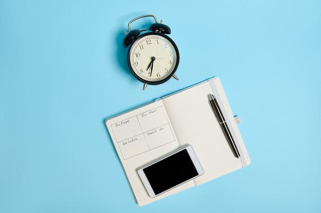 Flache lage eines handy-smartphones und eines tintenstiftes auf einem offenen notizbuch mit zeitplan neben einem schwarzen wecker, einzeln auf farbigem hintergrund mit kopierraum. zeitmanagement und terminkonzepte