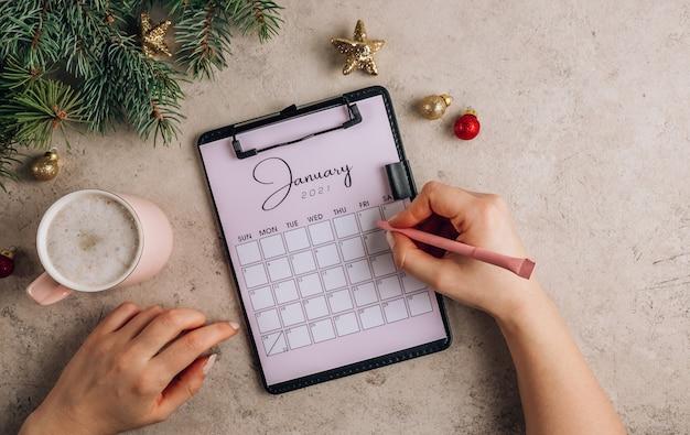 Flache lage eines teils des kalenders mit januar-schriftzug mit einer tasse kaffee
